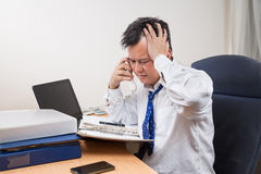 Stressful and frustrated Asian manager talking on telephone in o Stock Image