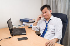 Stressful and frustrated Asian manager talking on telephone in o. Busy, stressful and frustrated Asian business manager talking on telephone in office Stock Photo