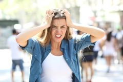 Stressful furious girl in the street. Front view portrait of a stressful furious girl looking at camera in the street Stock Image