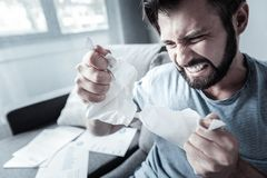 Stressful mad man tearing paper. Hate this job. Angry irritated bearded man ripping apart paper while screaming and clenching teeth Stock Photos
