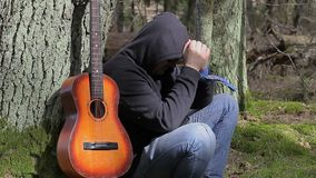 Stressful Man with guitar in the forest stock video footage