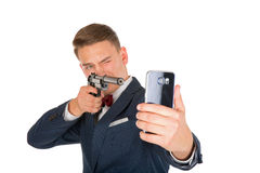 Stressful man. Photo of a man shooting a smartphone with a handgun stock images