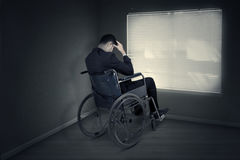 Stressful man sitting on the wheelchair near the window Royalty Free Stock Photos
