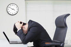 Stressful manager in office with clock on the wall Stock Photography