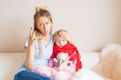 Mother frustrated about her child being sick. Stressful mother frustrated about her child being sick Royalty Free Stock Images