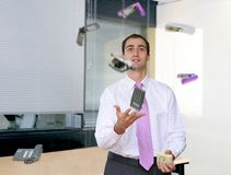 Stressful office life. Businessman juggling desk tools in an office Royalty Free Stock Photo