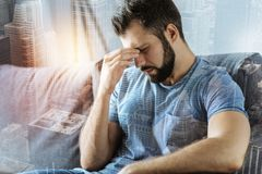 Stressful sad man sitting and having head ache. Trouble again. Stressful unshaken sad man sitting in the room on the sofa holding right hand near nose and Stock Image