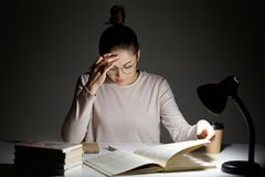 Stressful schoolgirl does home assigment, rewrites information from book in notebook, keeps hand on forehead, feels tired, works l royalty free stock photography
