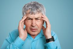 Stressful senior male dressed in formal shirt, wears smartwatch, keeps hands on temples, suffers from terrible headache, has unhap. Py expression, isolated over Stock Photography