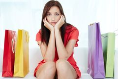 Stressful shopping. Portrait of young stressed brunette surrounded by paperbags Stock Photography