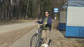Stressful woman near bus stop with bicycle. In summer day stock video footage
