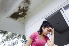 Stressful woman under damaged ceiling. Image of Asian woman looks stressful while sitting under damaged ceiling Stock Photos