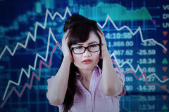 Stressful worker with declining stock market Stock Photo