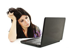 Stressful young woman working on laptop. On white background Royalty Free Stock Photo