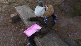 Stressig flicka med ryggsäcken och mapp på bänk arkivfilmer