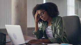 Stressig ung affärskvinna på skrivbordet genom att använda bärbara datorn arkivfilmer