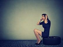 Stressige schreiende Frau beim Sitzen auf Reifen stockfotografie