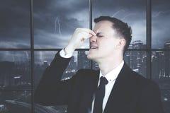 Stressiger Geschäftsmann, der im Büro die Stirn runzelt Lizenzfreies Stockfoto