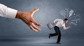 Stressiger Geschäftsmann, der von einer großen Hand läuft Lizenzfreies Stockbild