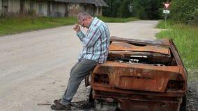 Stressiger Mann auf gebrannt hinunter Autowrack auf der Seite der Straße stock footage
