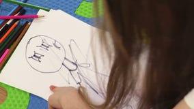 Stressiges Mädchen, das Puppe in der schwarzen Farbe zeichnend beendet stock footage