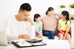 Stresu mężczyzna cyrklowania rachunki podczas gdy rodzinny obsiadanie na kanapie Fotografia Royalty Free