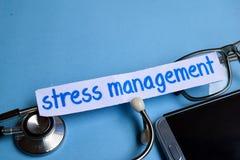 Stresu zarządzania inskrypcja z widokiem stetoskop, eyeglasses i smartphone na błękitnym tle, zdjęcia stock