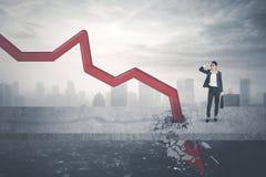 Stresujący biznesmen patrzeje opadającą strzała Obrazy Stock