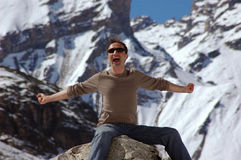 The Stretch. Happy man perched on rock in the swiss alps with arms stretched out; Photo shot in the afternoon;  In the background snow and glaciers of the swiss Stock Photography