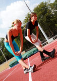 Stretch exercises. Two young girls stretching after jogging Stock Photo