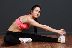 Stretch hamstring and back. Fitness woman smiling at the camera Royalty Free Stock Image