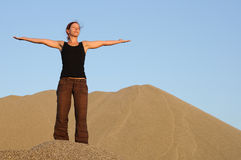 Stretch out arms. Athletic woman stretching out her arms in sand mountains scenic Stock Photo