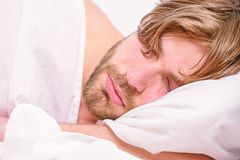 Stretch after wake up in the morning. Man eyes are closed with relaxation. Man with eyes still closed reaching button on stock photos