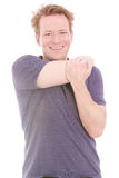 Stretch your shoulder. Young smiling man stretching his shoulder muscles - isolated on white royalty free stock photo