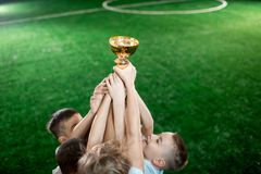 Boys with award. Stretched arms of little footballers holding gold award on background of green pitch royalty free stock photography