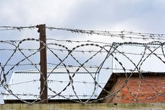 Stretched barbed wire against the sky and the roof Royalty Free Stock Photo