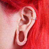 Stretched ear lobe piercing Royalty Free Stock Images
