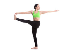 Stretched hand grasps big toe yoga asana. Serene sporty girl, doing fitness stretching exercises, standing in yoga posture utthita hasta Padangustasana, extended Royalty Free Stock Photos