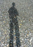 Stretched man shadow on dry river bed. Royalty Free Stock Photography