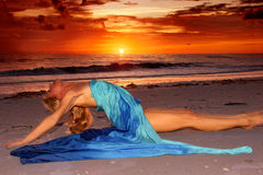 Stretched out on beach. A long haired blonde woman is stretched out on the beach at suset in profile with her legs straight out and her back arched as she looks Royalty Free Stock Photography