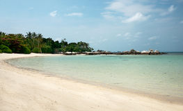 Stretched out white sand beach with natural rock formation at the coastline on the horizon in Belitung Island. Stock Photography