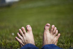 Stretched toes relaxing  on Grass. View of feet lying and relaxing on grass with toes stretched Royalty Free Stock Photos