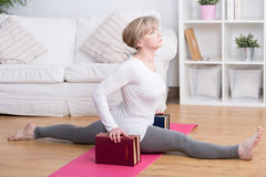 Stretched woman and splits. Stretched retired woman doing splits at yoga exercises Stock Photography