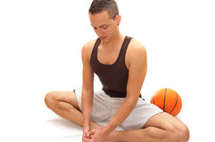 Stretching. A basketball player stretches himself before a big game Stock Photo