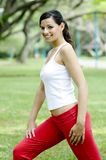 Stretching. An attractive fit young woman stretching in the park (shallow depth of field used royalty free stock images