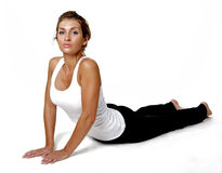 Stretching. A beautiful woman stretches lying face down on a white floor Stock Photo