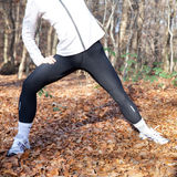 Stretching. A young woman warming up before going for a run in the woods Royalty Free Stock Photography