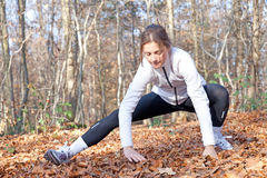 Stretching. A young woman warming up before going for a run in the woods Stock Photography
