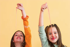Stretching. Two girls stretching a chewing gum from they're mouth Stock Photos
