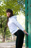 Stretching. Beautiful brawny sport woman stretching near vertical sport bar outdoors in the park on a bright sunny day Royalty Free Stock Photography